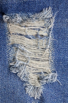 De blauwe gescheurde textuur van denimjeans.
