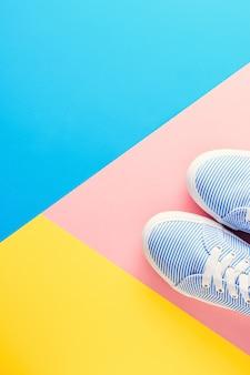 De blauwe gestreepte tennisschoenen op gekleurde pastelkleur achtergrond hoogste meningsvlakte leggen