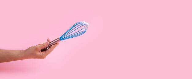 De blauwe handleiding zwaait in de hand over roze achtergrond, dessert kookconcept, panoramische mock-up
