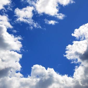 De blauwe lucht met veel witte wolken van verschillende groottes