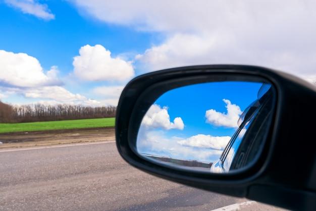 De blauwe lucht met witte wolken wordt overdag weerspiegeld in de autospiegel
