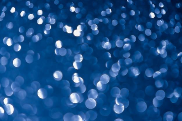 De blauwe marineachtergrond schittert de zilveren abstracte lichte glinsterende sterren van de kerstmistextuur op bokeh. glitter vintage lichten achtergrond