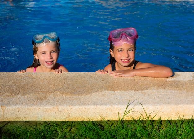 De blauwe meisjes van ogenkinderen op het blauwe poolsideside glimlachen