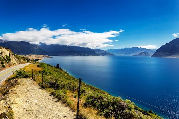 De blauwe mening van meer hawea op een de zomer zonnige dag, zuideneiland, nieuw zeeland