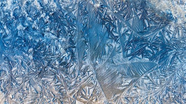 De blauwe mooie patronen van de de wintervorst, de abstracte textuur van vorstbloemen op de weg