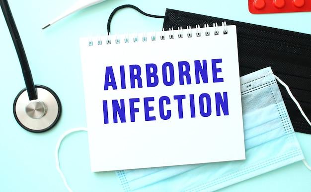 De blauwe tekst airborne infection is geschreven in een notitieboekje dat op een blauwe achtergrond naast medische maskers ligt
