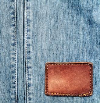 De blauwe textuur van denimjeans met leeg etiket