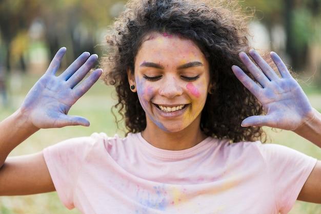 De blauwe verf behandelde handen stellen van vrouw bij holi