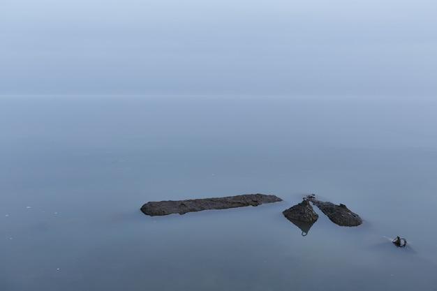 De blauwe zee versmelt in de vroege ochtend in absolute rust met de lucht