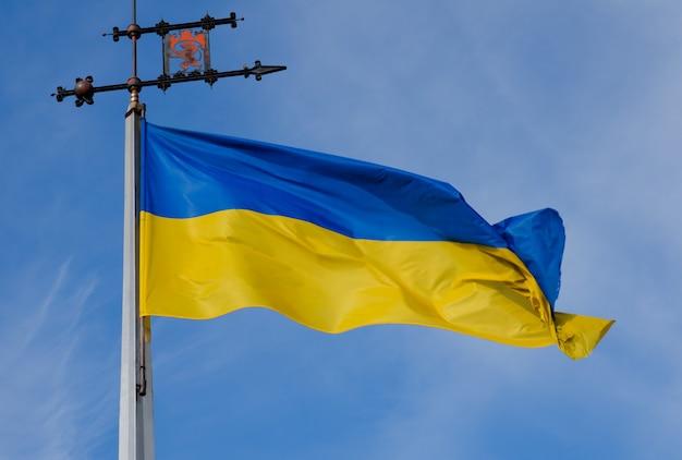 De blauwgele oekraïense vlag met het embleem van lviv op de vlaggenmast.