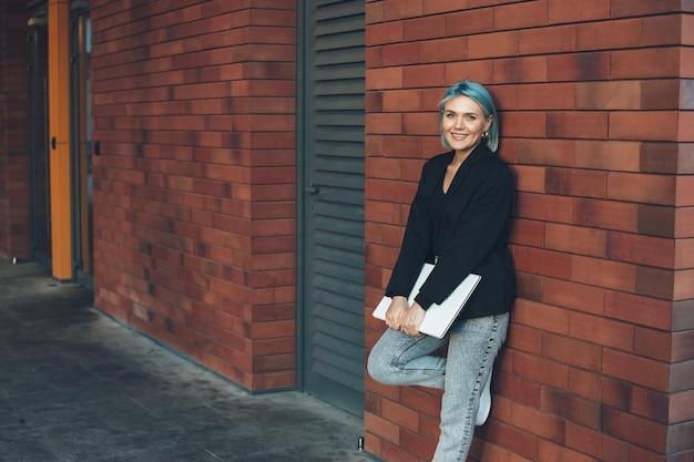 De blauwharige vrouw met laptop stelt op een bakstenen muur in de stad die bij camera glimlacht