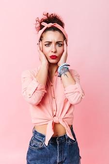De blauwogige vrouw in pin-upoverhemd en spijkerbroek onderzoekt de camera met bezorgdheid. krullend meisje met rode lippen poseren over roze ruimte.
