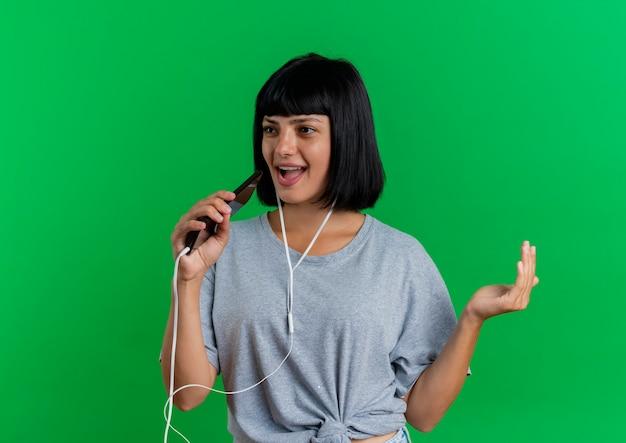 De blije jonge donkerbruine kaukasische vrouw op hoofdtelefoons houdt telefoon die beweert te zingen geïsoleerd op groene achtergrond met exemplaarruimte te zingen