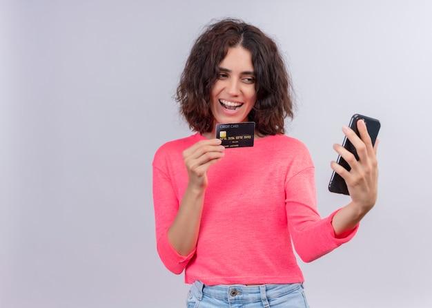 De blije jonge mooie kaart van de vrouwenholding en mobiele telefoon op geïsoleerde witte muur met exemplaarruimte