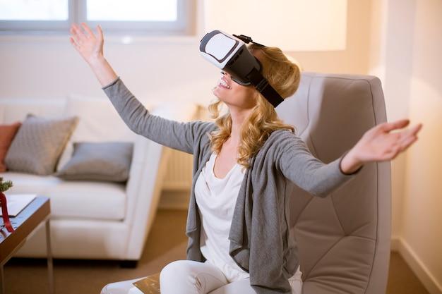De blije jonge spelen van de vrouwen speelcomputer met virtuele werkelijkheid googles thuis