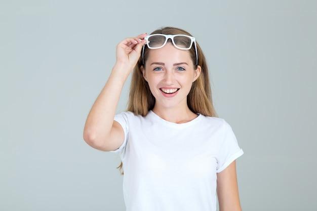 De blije jonge vrouw hief haar glazen over haar hoofd op, geïsoleerd op grijs