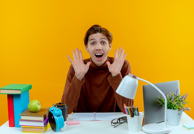 De blije jonge zitting van de studentenjongen aan bureau met de hand van schoolhulpmiddelen rond gezicht