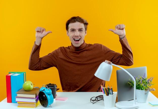 De blije jonge zitting van de studentenjongen aan bureau met schoolhulpmiddelen wijst naar zichzelf