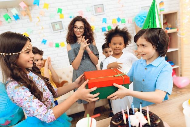 De blije jongen in feestelijke hoed ontvangt gift van meisje.