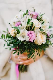 De bloemboeket van het huwelijk in de handen van de bruid