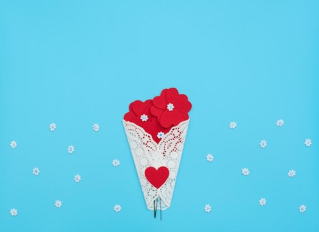 De bloemen gemaakt van vilten harten gewikkeld in een witte kanten bundel op blauwe achtergrond met kleine bloemen