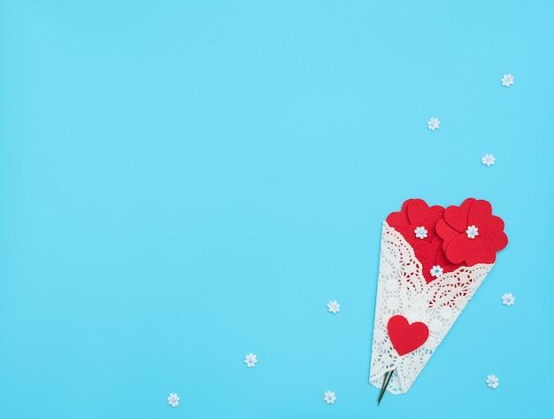 De bloemen gemaakt van vilten harten gewikkeld in een witte kanten bundel op blauwe achtergrond