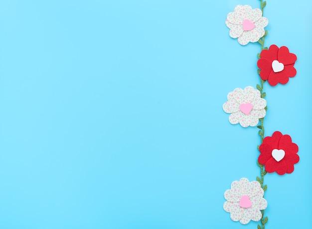 De bloemen gemaakt van vilten harten met groene bladeren op blauwe achtergrond