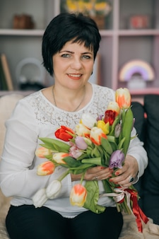 De bloemen van de vrouwenholding in haar hand thuis