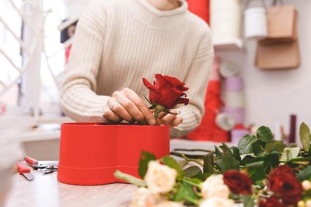 De bloemistvrouw die van de bloemenwinkel doos met rode rozen maken.