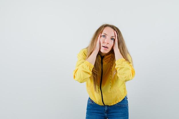 De blonde dame die het hoofd vastklemt met dient jas, jeans in en kijkt geïrriteerd.