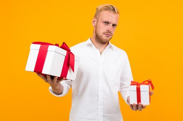 De blonde europese jonge mens in een wit overhemd houdt giftdozen op een geel