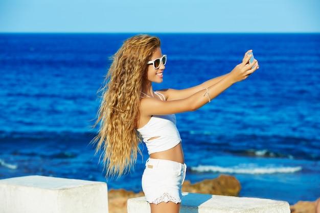 De blonde foto van het tienermeisje selfie op smartphone bij strand