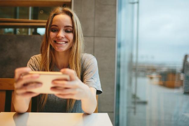 De blonde gebruikt de telefoon. meisje en smartphone. een vrouw zit in een café met een mobiele telefoon