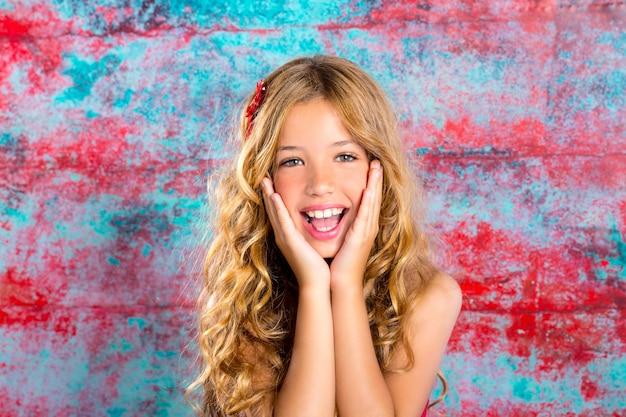 De blonde gelukkige het glimlachen uitdrukking van het jong geitjemeisje dient gezicht in
