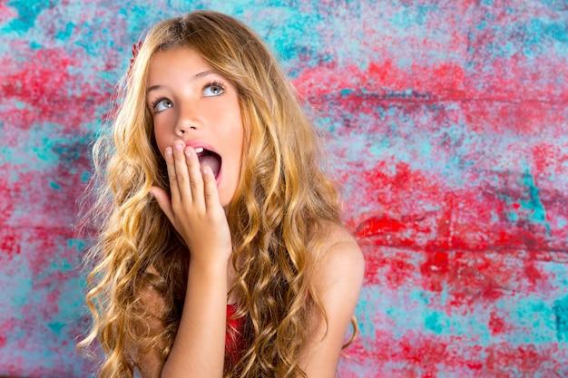 De blonde jong geitjemeisje verraste uitdrukking dient gezicht in