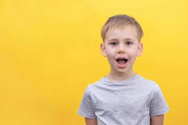 De blonde jongen kijkt verrast naar de camera met zijn mond open op een gele achtergrond