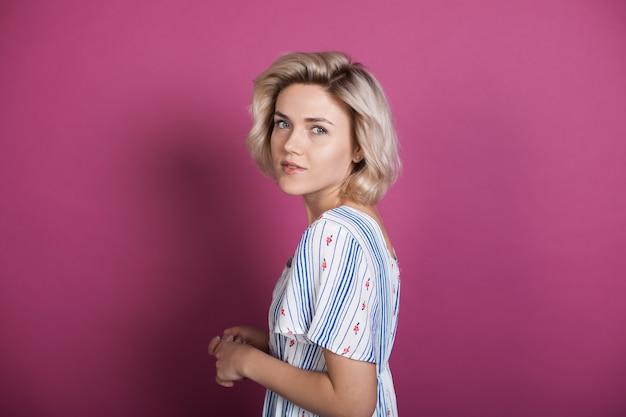 De blonde kaukasische vrouw die een modern overhemd draagt, kijkt terug naar de camera op een violette studiomuur