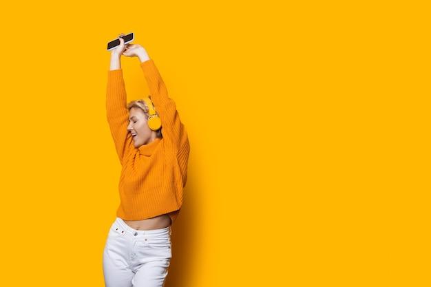 De blonde kaukasische vrouw met hoofdtelefoons houdt een telefoon vast die aan muziek op een gele muur met vrije ruimte luistert die een sweater draagt