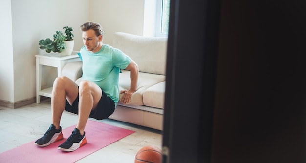 De blonde man die sportkleding draagt, doet thuis fitness