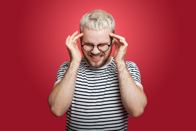 De blonde man met borstelhaar is gebaren hoofdpijn zijn hoofd aan te raken en op een rode studiomuur te schreeuwen