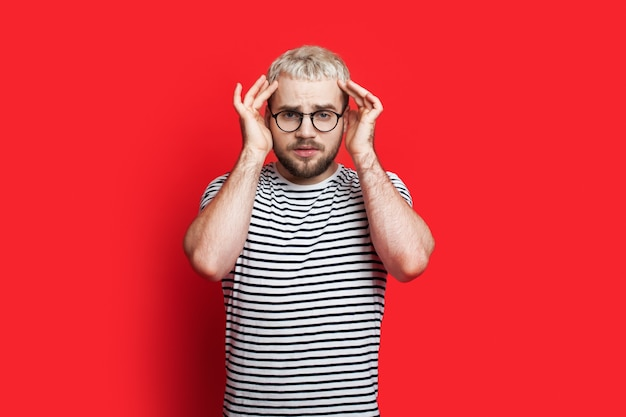 De blonde man met bril gebaart hoofdpijn op een rode studiomuur wat betreft zijn hoofd