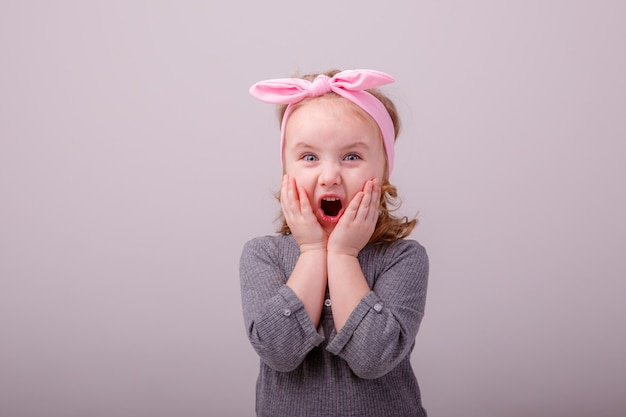 De blonde van het babymeisje toont verschillende emotiesverrassing, vreugde