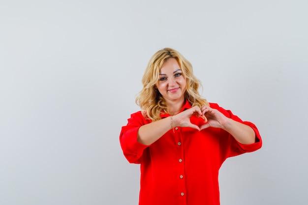 De blonde vrouw die hartvorm toont met dient rode blouse in en kijkt mooi, vooraanzicht.