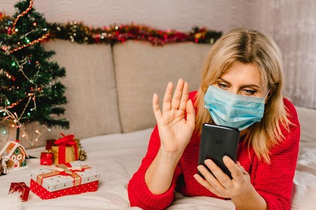 De blonde vrouw die masker draagt en communiceert of maakt orde op mobiele telefoon. vrouw koopt cadeautjes, bereidt zich voor op kerstmis, geschenkdoos in de hand. online dating.
