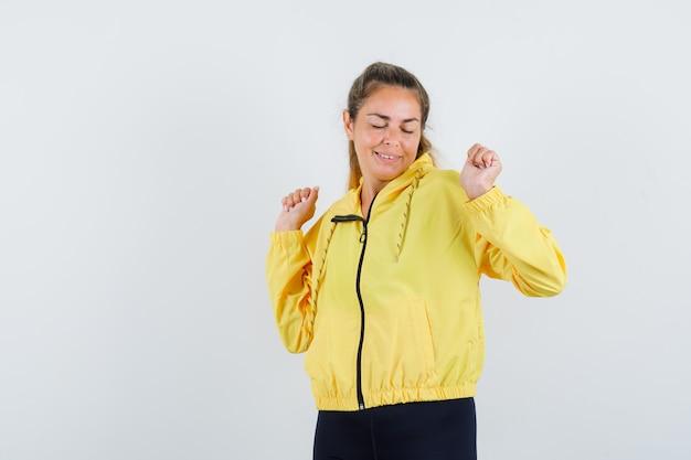 De blonde vrouw die winnaar toont stelt in geel bomberjack en zwarte broek en kijkt gelukkig