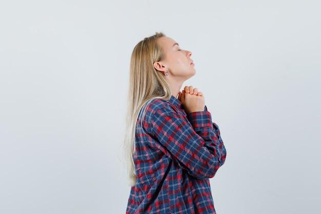 De blonde vrouw die zich in gebed bevindt stelt in geruit overhemd en kijkt gericht, vooraanzicht.