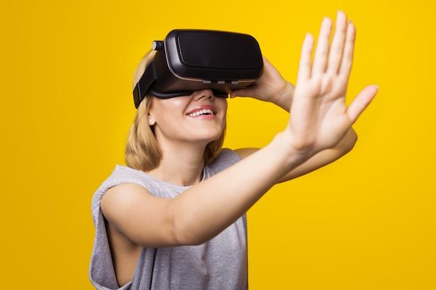De blonde vrouw op een gele muur draagt een virtual reality-headset om iets aan te raken en te glimlachen