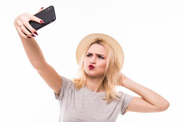 De blonde vrouw trekt een eendgezicht om een foto voor haar vriend te verzenden