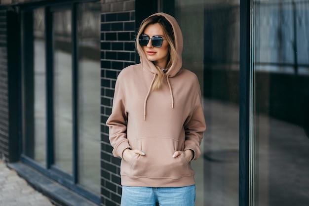 De blonde vrouw van fasion in bruine oversized hoodieglazen en blauwe spijkerbroek