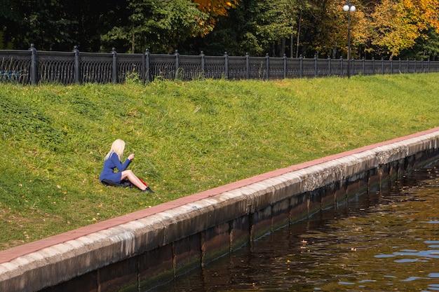 De blonde vrouw zit alleen aan de oever van de rivier.